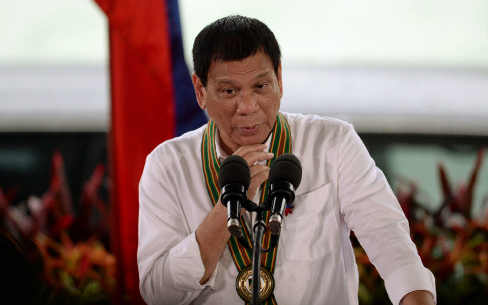 """This photo taken on October 4, 2016 shows Philippine President Rodrigo Duterte gesturing as he delivers a speech during a """"Talk to the Troops"""" visit to army personnel in Manila.  Duterte's popularity has soared during his first three months in office, an independent survey showed on October 6, in an apparent endorsement by Filipinos of his brutal crime crackdown. / AFP PHOTO / TED ALJIBE"""