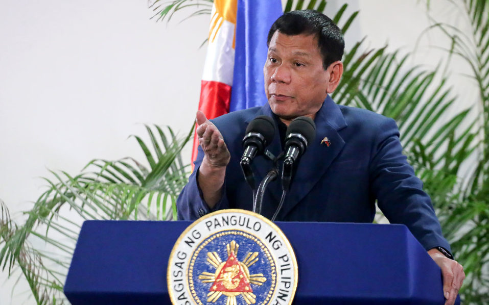 """Philippine President Rodrigo Duterte gestures as he speaks at the Davao International Airport after arrving back from a state visit to Brunei and China on October 22, 2016. Philippine President Rodrigo Duterte said on October 22 he would not sever his nation's alliance with the United States, as he clarified his announcement that he planned to """"separate"""". / AFP PHOTO / MANMAN DEJETO"""