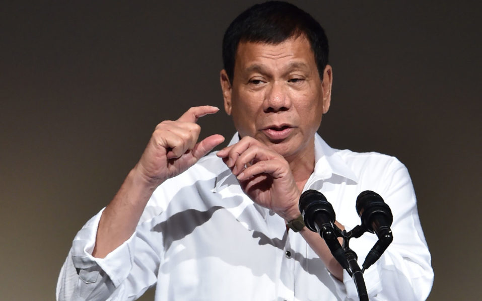 """Philippines' President Rodrigo Duterte delivers a speech at the Philippines' Economic Forum in Tokyo on October 26, 2016.  Duterte was set on October 26 to persuade Japanese executives his country is """"open for business"""", after upending traditional alliances by insulting the US and making overtures to China. / AFP PHOTO / KAZUHIRO NOGI"""