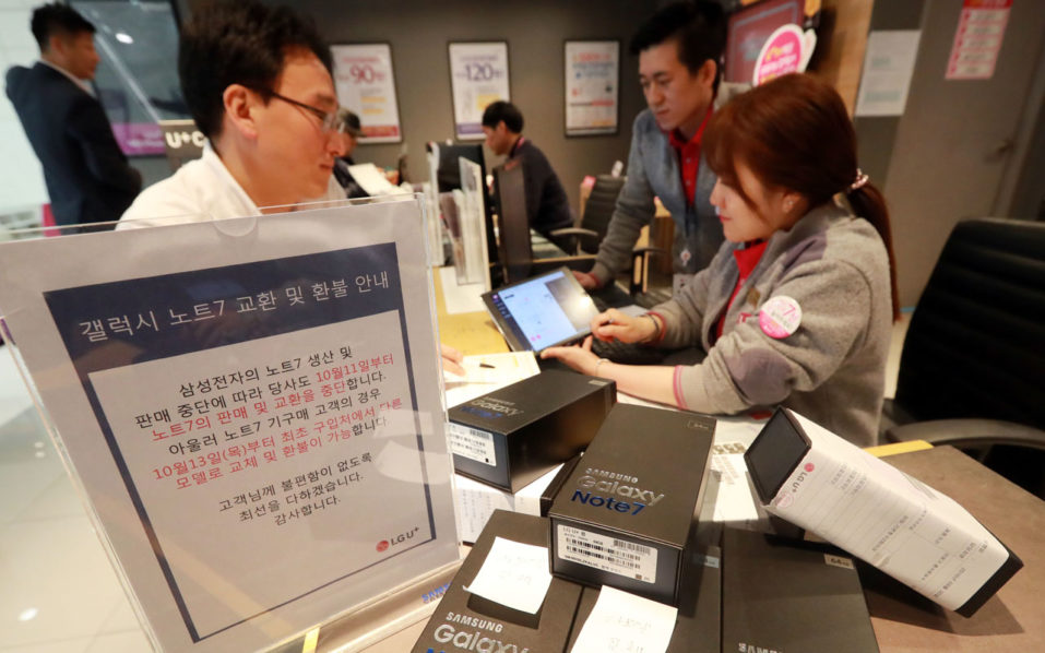 Customers return their Samsung Note 7 mobile phones at a dealership in Seoul on October 13, 2016. South Korea's central bank cut its growth outlook for next year to 2.8 percent in the wake of Samsung Electronics' damaging recall crisis and its impact on the economy. / AFP PHOTO / YONHAP / yonhap /