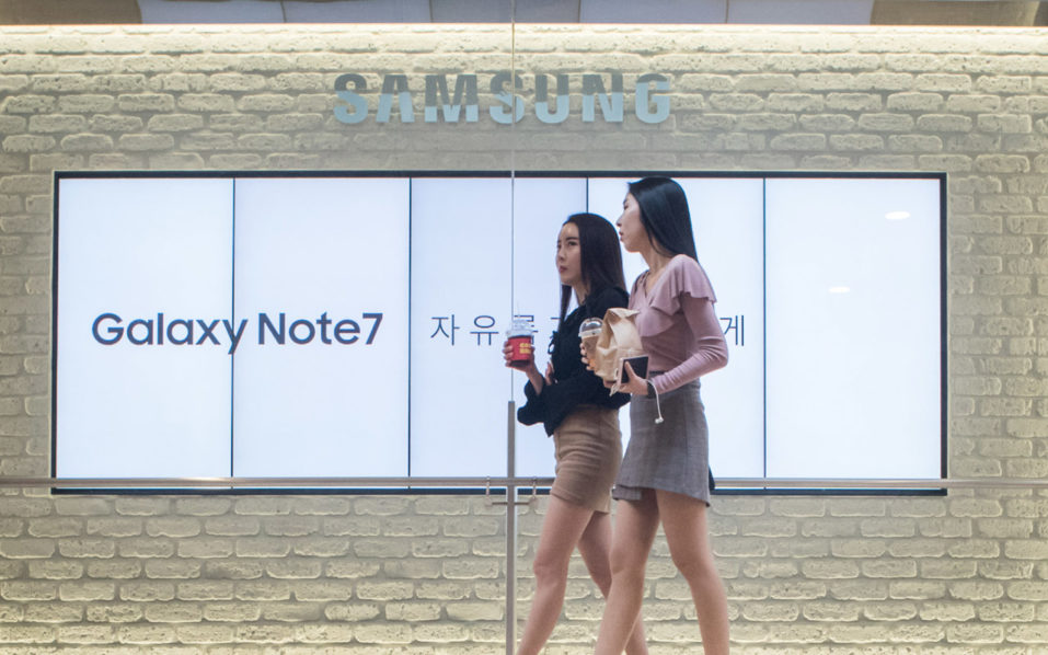 Two women walk past an advertisement for Samsung's Galaxy Note 7 device at a Samsung store in the Gangnam district of Seoul on October 11, 2016. Samsung told customers worldwide to stop using their Galaxy Note 7 smartphones as it struggled to contain a snowballing safety crisis that threatens to derail the powerhouse global brand. / AFP PHOTO / Ed Jones