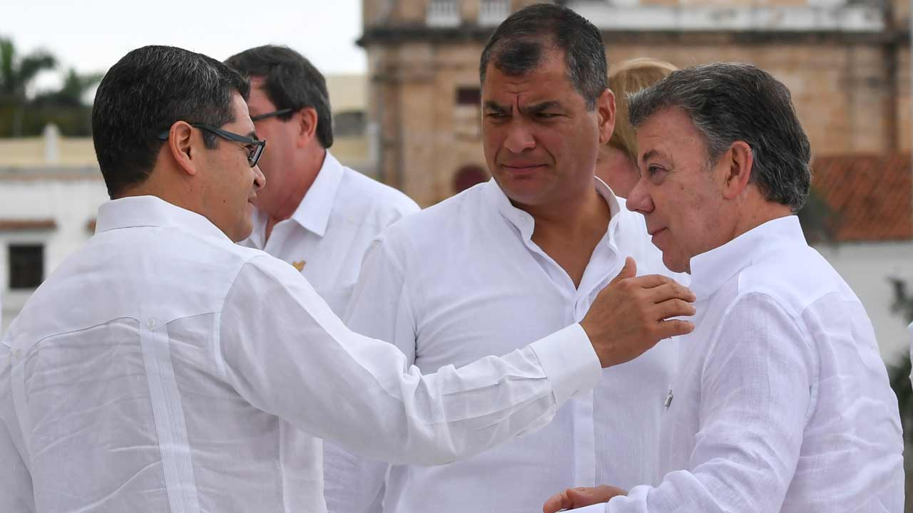 Colombian President Juan Manuel Santos (R) is greeted by Honduran President Juan Orlando Hernandez (L) next to Ecuadorean President Rafael Correa during the family photo of the XXV Ibero-American Summit in Cartagena, Colombia, on October 29, 2016. The two-day Ibero-American Summit, started October 28 amid concerns over instability in Venezuela and Colombia's troubled peace drive. Luis Acosta / AFP