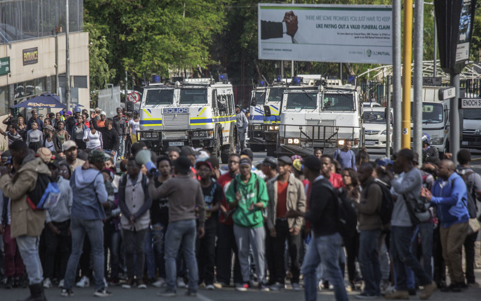 Armoured police vehicles are parked in the distance as students from the University of Witwatersrand gather in a street of Johannesburg as they demonstrate to call for free higher education on October 20, 2016.  Weeks of protests at South African universities have targeted tuition fees -- but students say they are also about racism and inequality in a society still plagued by the legacy of apartheid. / AFP PHOTO / GIANLUIGI GUERCIA