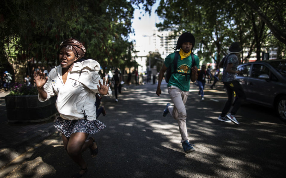 Demonstrators disperse during a protest in Johannesburg on September 21, 2016 over higher tuition fees. South African police fired stun grenades and rubber bullets to disperse protesting students in central Johannesburg, in further outbreaks of unrest over higher tuition fees. / AFP PHOTO / MARCO LONGARI