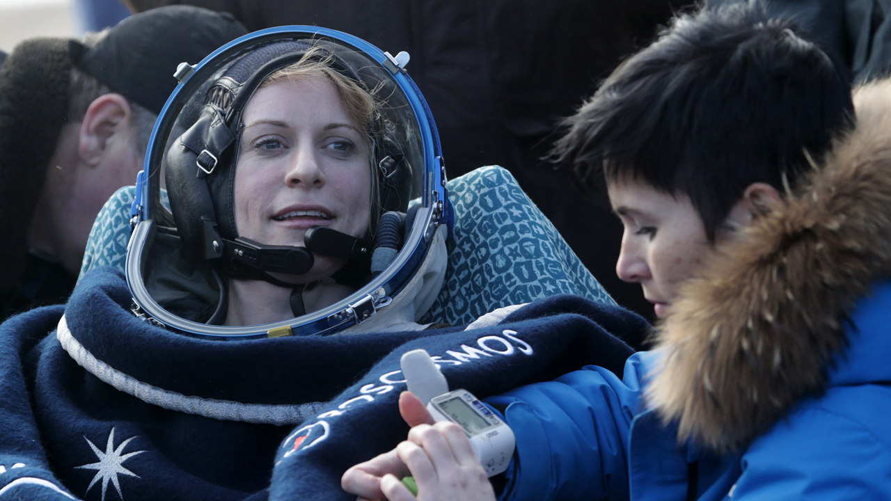 US astronaut Kate Rubins rests in a chair outside the Soyuz MS space capsule after she and two other astronauts landed in a remote area about 150 kms (90 miles) southeast of the Kazakh town of Dzhezkazgan on October 30, 2016. Three astronauts landed safely in Kazakhstan on October 30 following a 115-day mission aboard the the International Space Station, including US astronaut Kate Rubins, the first person to sequence DNA in space. / AFP PHOTO / POOL / Dmitri Lovetsky