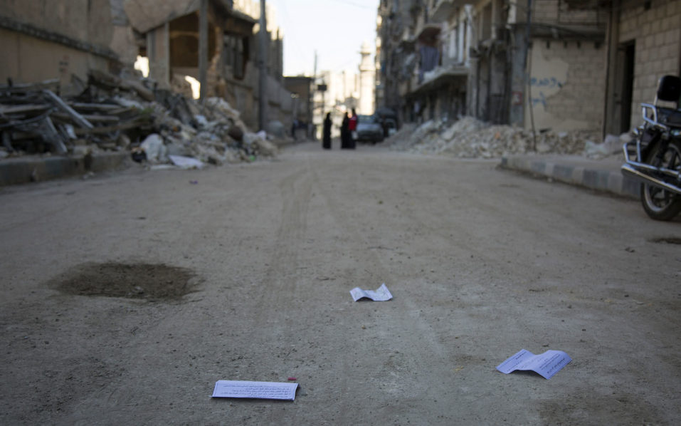 "Flyers reportedly distributed by the government encouraging people to leave a rebel-held area in the northern embattled city of Aleppo are seen lying in the street on October 20, 2016.  A ""humanitarian pause"" in the Syrian army's Russian-backed assault on Aleppo took effect but despite a drop in violence there was little sign residents were heeding calls to leave.  / AFP PHOTO / KARAM AL-MASRI / TO GO WITH AFP STORY BY KARAM AL-MASRI"