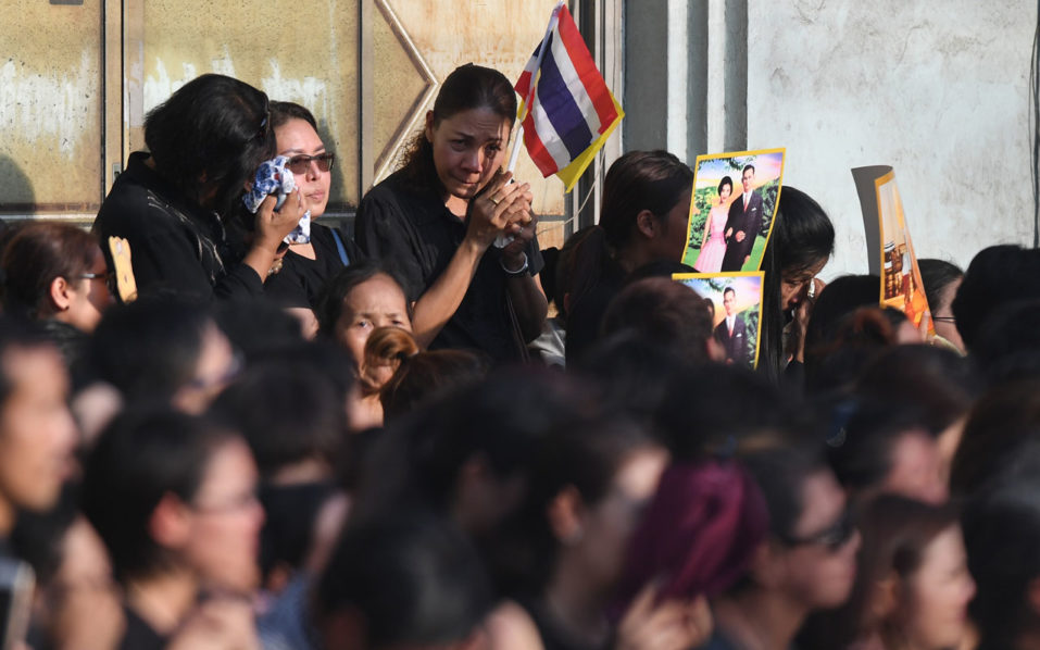 Onlookers weep as massive crowds line the streets during the procession of Thai King Bhumibol Adulyadej's body to his palace in Bangkok on October 14, 2016. Bhumibol, the world's longest-reigning monarch, passed away aged 88 on October 13, 2016 after years of ill health, removing a stabilising father figure from a country where political tensions remain two years after a military coup. / AFP PHOTO / MANAN VATSYAYANA