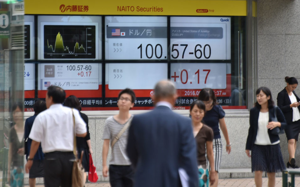 Pedestrians walk past an electronics quotation board displaying the current exchange rate of the Japanese yen against the US dollar in Tokyo  / AFP PHOTO / KAZUHIRO NOGI