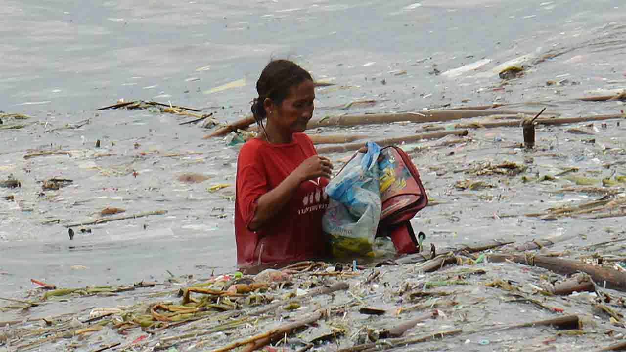 A woman collects recyclable materials washed ashore, after Typhoon Sarika passed north of the capital overnight but hit parts of northern Luzon island. Typhoon Sarika smashed into the main Philippine island of Luzon early on October 16, ripping off roofs, toppling power lines and forcing more than 12,000 people to flee to safer ground, officials said. / AFP PHOTO / TED ALJIBE