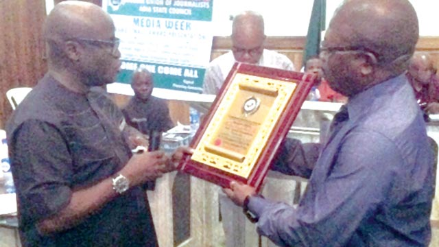 Abia State Commissioner for Works, Mr. Eziuche Ubani (left), presenting award to former Abia State governor, Mr. Theodore Orji, being received by his Media Adviser, Mr. Don Norman Obinna, last Friday… in Umuahia