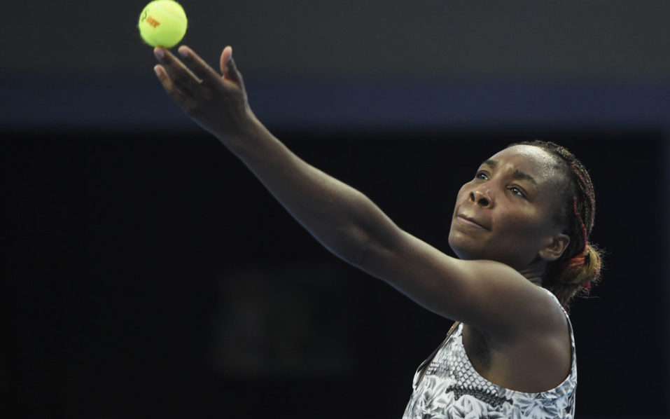Venus Williams of the US serves against China's Peng Shuai during their women's singles first round match at the China Open tennis tournament in Beijing on October 3, 2016.  / AFP PHOTO / FRED DUFOUR