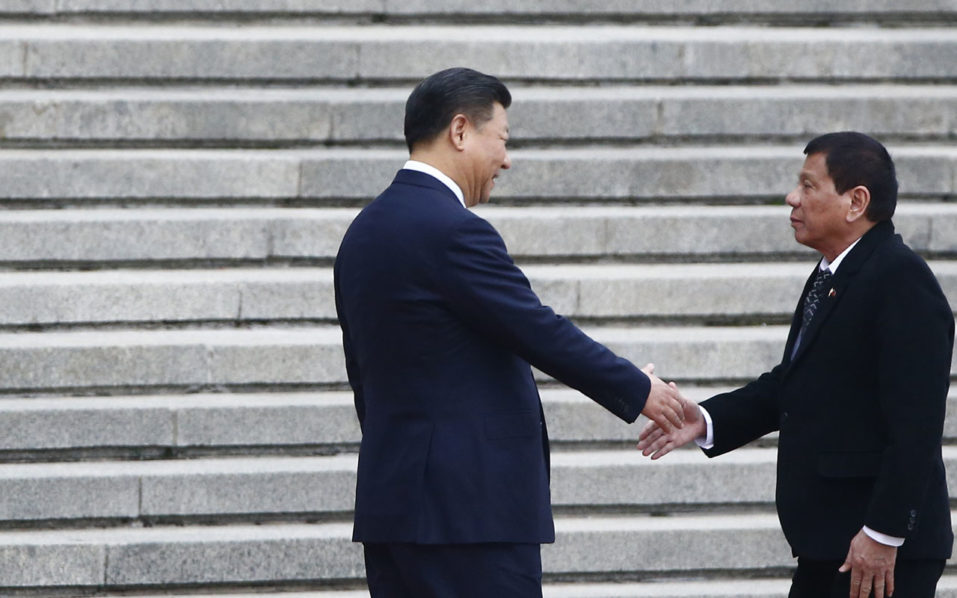 "Philippines President Rodrigo Duterte (R) and Chinese President Xi Jinping (L) shake hands as they attend a welcoming ceremony at the Great Hall of the People in Beijing, China, October 20, 2016. Duterte said it was ""time to say goodbye"" to the US during a visit to China on October 19, as the combative leader reconfigures his country's diplomatic alliances / AFP PHOTO / POOL / THOMAS PETER"