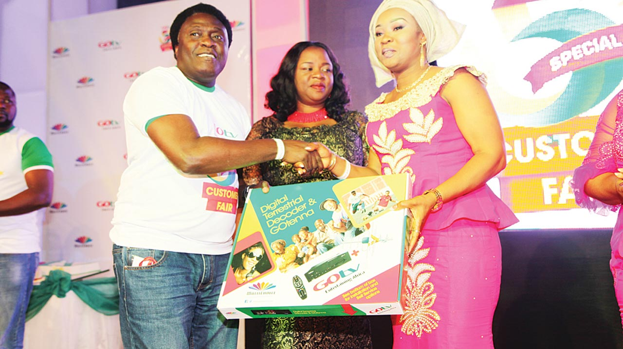 General Manager, GOtv, Akinola Salu, presenting GOtv decoder to Mrs. Ogochi Onah, wife of Commissioner for Lands and Urban Developments, Enugu State, while Mrs. Uche Lilian Nweke watches on at GOtv's 5th anniversary Customer Fair held at DE DOME last Saturday… Enugu