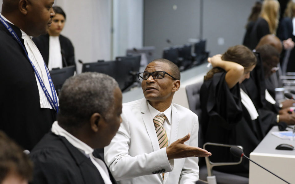 "Narcisse Arido (C) of the Central African Republic talks with his lawyer in the courtroom of the International Criminal Court (ICC) in The Hague, on October 19, 2016.  International judges on October 19, 2016 found former Congolese vice president Jean-Pierre Bemba and four aides guilty of corrupting witnesses, by bribing them with money and laptops to lie during the testimony to his war crimes trial. The case was ""about clear, and downright criminal behaviour of the five accused... that resulted in serious offences against the administration of justice,"" judge Bertram Schmitt told the International Criminal Court as handed down the verdict.   / AFP PHOTO / POOL / Michael Kooren / Netherlands OUT"