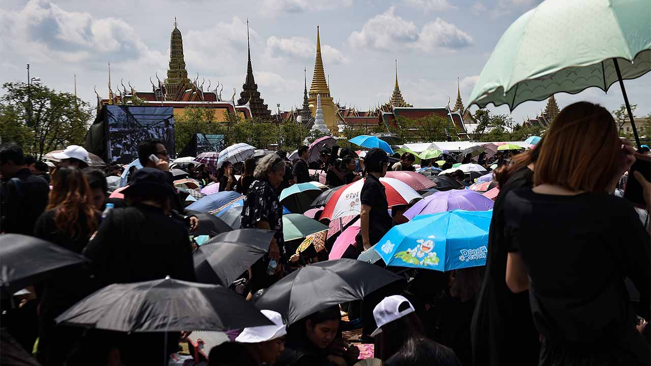 Thousands of mourners clad in black gather in front of the Grand Palace to pay respects to the late Thai King Bhumibol Adulyadej in Bangkok on October 22, 2016. Thailand's King Bhumibol Adulyadej died at the age of 88 on October 13 after years of ill health, ending a seven-decade reign and leaving the politically divided nation without its key pillar of unity. / AFP PHOTO / LILLIAN SUWANRUMPHA