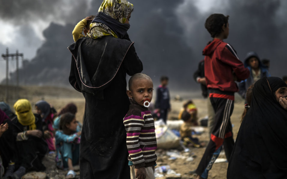 Iraqi families who were displaced by the ongoing operation by Iraqi forces against jihadistds of the Islamic State group to retake the city of Mosul, are seen gathering in an area near Qayyarah on October 24, 2016. The UN refugee agency is preparing to receive 150,000 Iraqis fleeing fighting around the Islamic State group-held city of Mosul within the next few days, its chief said./ AFP PHOTO / BULENT KILIC