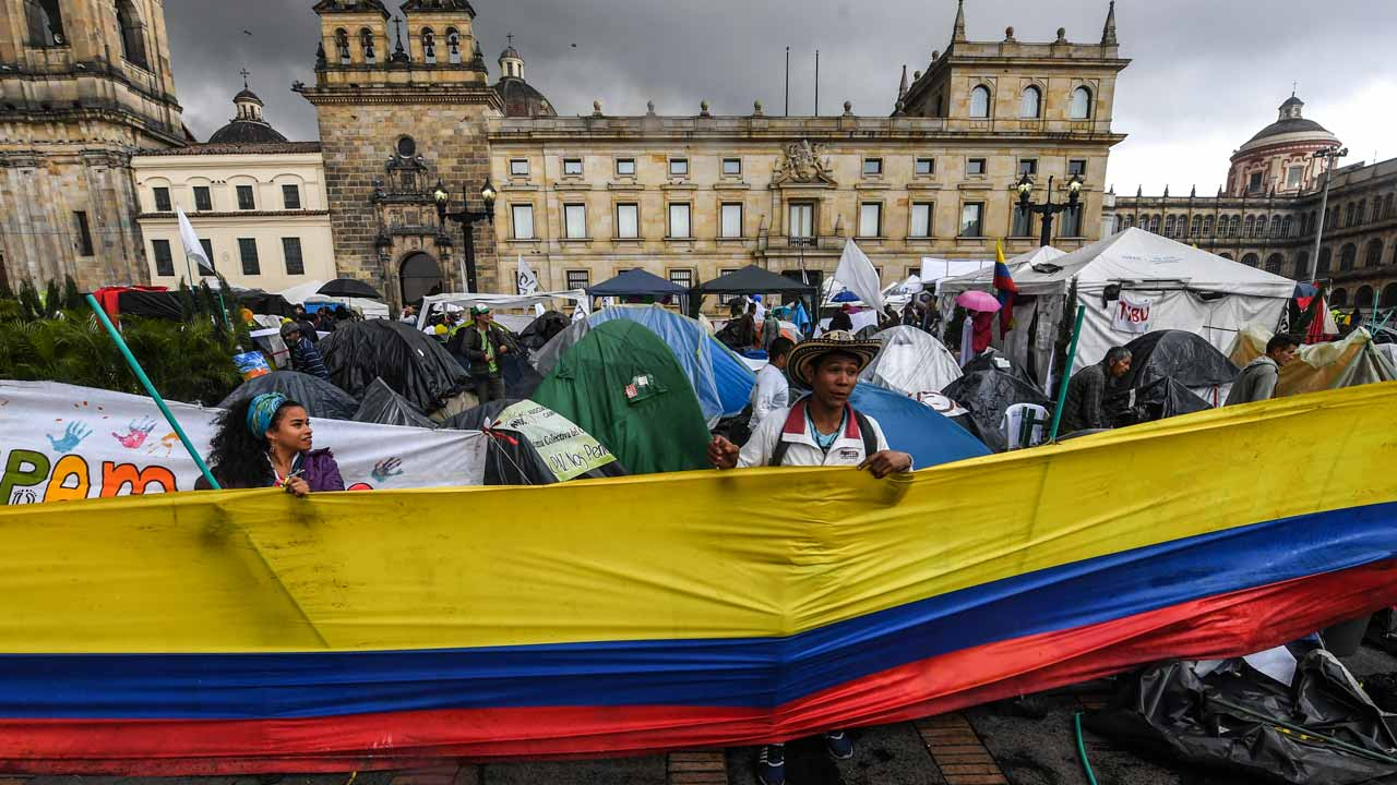 People take part in a demo for the immediate implementation of the agreement between the Colombian government and the FARC guerrillas at Bolivar Square in Bogota on November 18, 2016. PHOTO: Luis Acosta / AFP