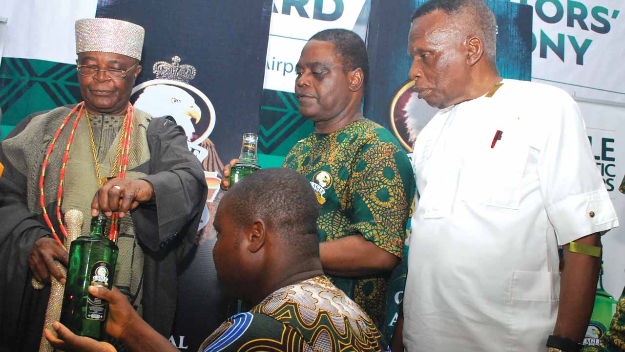 Oba Gbadebo pours libation with Eagle schnapps whilethe MD Intercontinental Distillers Limited, Patrick Anegbe and Chairman, Dr. Ishmael Igbani,look on.