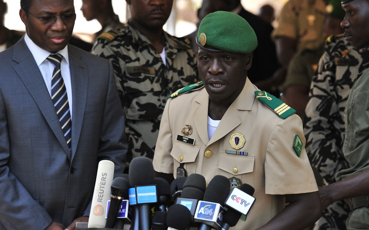 Malian junta leader captain Amadou Sanogo (C) speaking next to Burkina Faso's Foreign Minister Djibrill Bassole (L) during a declaration at the Kati military camp near Bamako. Amadou Sanogo, a former army captain who staged a military coup in Mali in 2012, went on trial on November 30, 2016 charged with the murder of several soldiers whose bodies were found in a mass grave. / AFP PHOTO / ISSOUF SANOGO