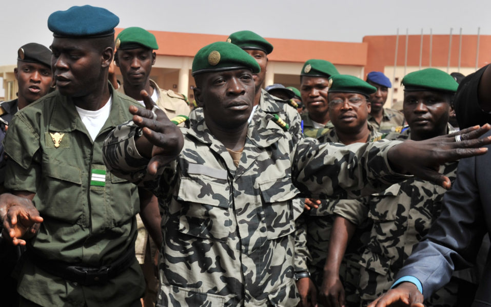 Malian military junta leader Amadou Sanogo (C) arriving at Bamako airport in Bamako. Amadou Sanogo who led Mali's 2012 coup against then president Amadou Toumani Toure will stand trial on November 30 for murder and collusion over the massacre of soldiers who opposed the takeover. / AFP PHOTO / ISSOUF SANOGO
