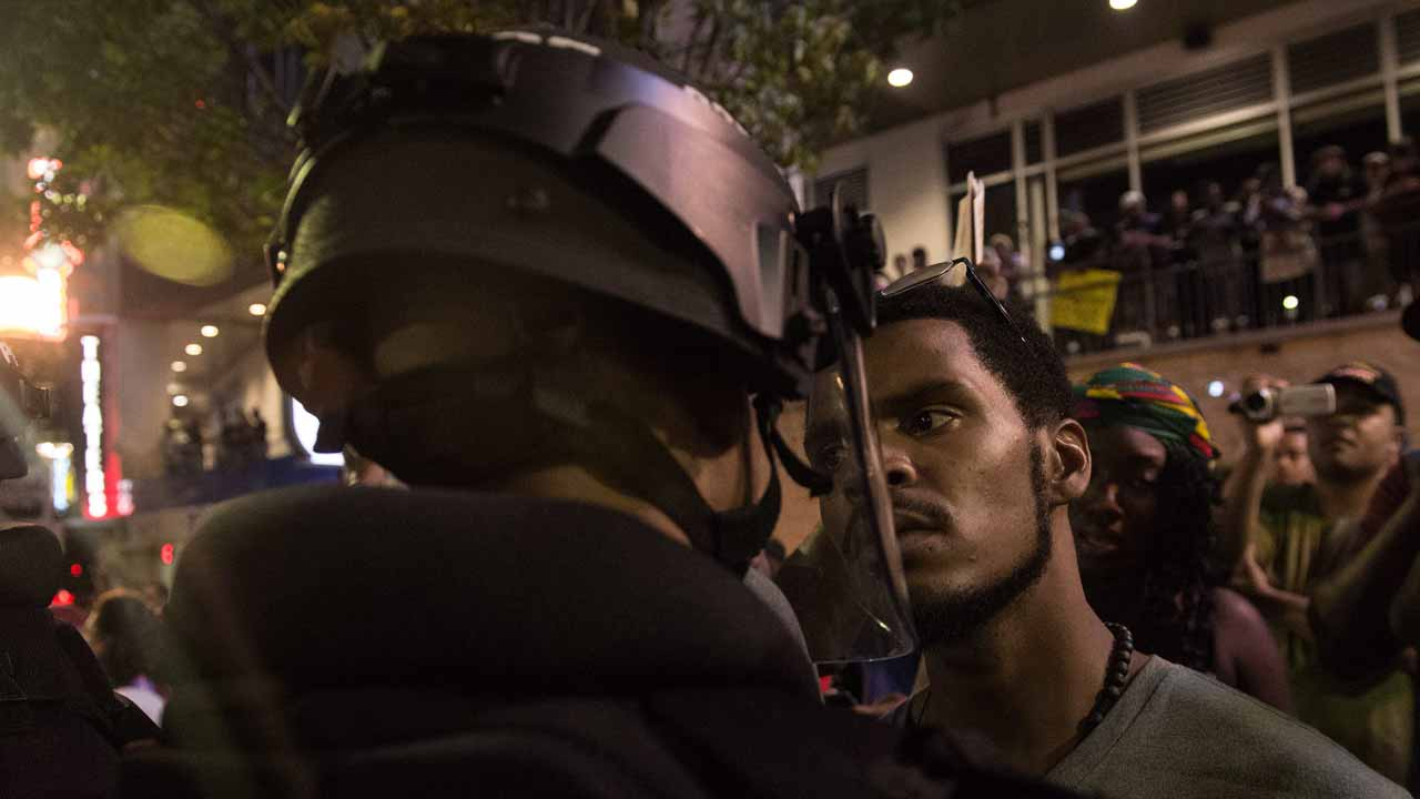 AFP PICTURES OF THE YEAR 2016 A protester stares at riot police during a demonstration against police brutality in Charlotte, North Carolina, on September 21, 2016, following the shooting of Keith Lamont Scott the previous day. A protester in Charlotte, North Carolina was fatally shot by a civilian during a second night of unrest after the police killed a black man, officials said. NICHOLAS KAMM / AFP
