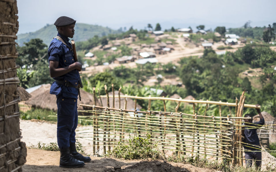 (FILES) This file photo taken on July 16, 2016 shows a Congolese policeman standing guard in the village of Buleusa. Tensions are high between Hutus and Kobos since the population started to return to the village after its evacuation by Rwandan Hutus Rebels (FDLR) in November 2015. At least 34 civilians were killed on November 27, 2016 in ethnic violence in restive eastern Democratic Republic of Congo, authorities said. / AFP PHOTO / Eduardo Soteras