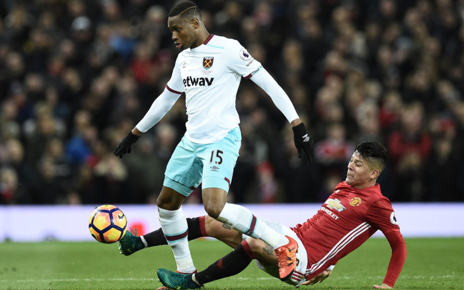 Manchester United's Argentinian defender Marcos Rojo (R) tackles West Ham United's Senegalese striker Diafra Sakho (L) during the English Premier League football match between Manchester United and West Ham United at Old Trafford in Manchester, north west England, on November 27, 2016. / AFP PHOTO / Oli SCARFF /