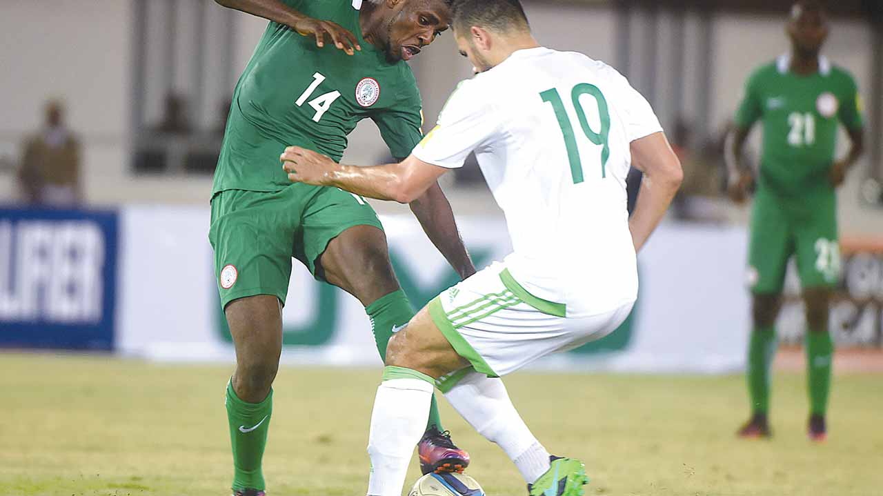 Super Eagles' forward, Kelechi Iheanacho (left) tries to beat Algeria's Mehdi Abeid during their 2018 FIFA World Cup African Zone Group B qualifier at the Godswill Akpabio Stadium, Uyo … on November 12, 2016. PHOTO: AFP.