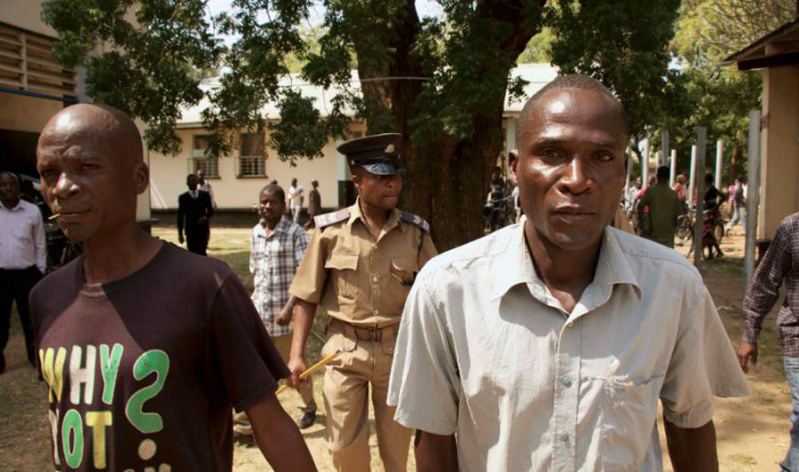 "Eric Aniva (right), known as a ""hyena"" arrives to the Magistrate Court on August 15, 2016 in Nsanje (AFP Photo/Eldson Chagara)"