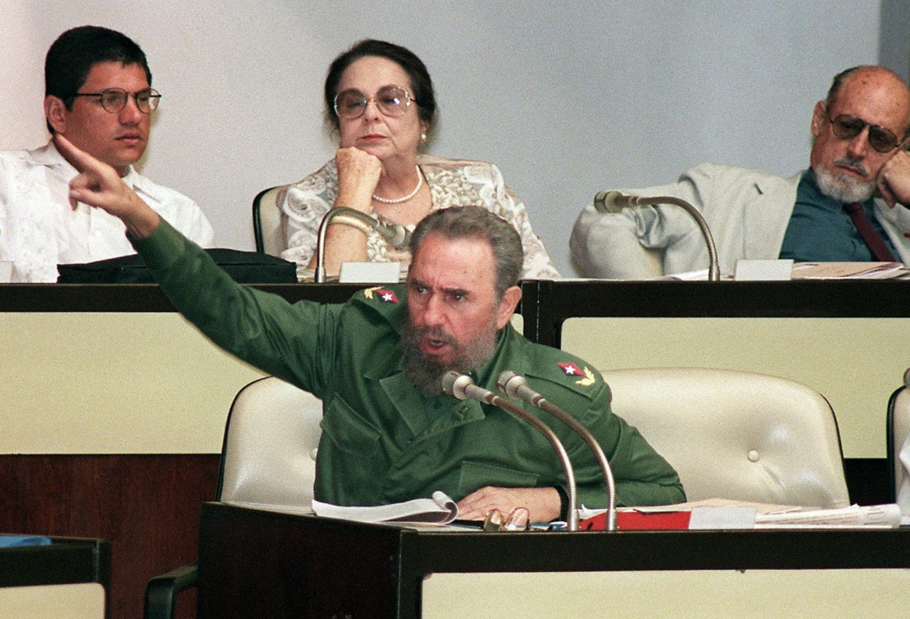 "(FILES) This file photo taken on July 21, 1998 shows Cuban President Fidel Castro pointing to the exit door of the Cuban parliament as he addresses foreign press correspondents working in Cuba 21 July accusing them of ""discrediting socialism, demoralizing the Cuban revolution by using lies and schemes of all sort"" during the parliament's opening session in Havana. AFP PHOTO / ADALBERTO ROQUE"