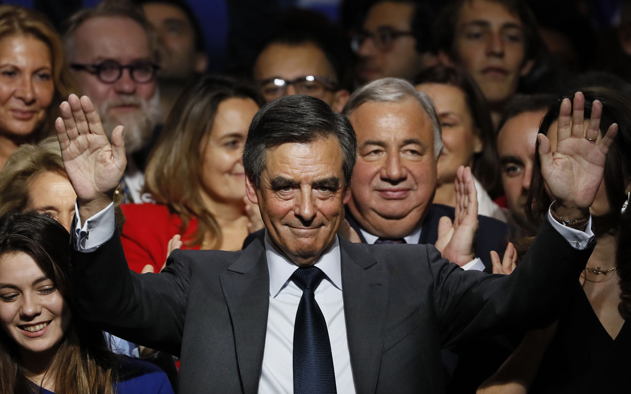 Francois Fillon (C), candidate for the right-wing primaries ahead of the French 2017 presidential election, waves at the end of a speech during a campaign rally in Paris, on November 25, 2016, ahead of the primary's second round on November 27/ AFP PHOTO / Thomas SAMSON