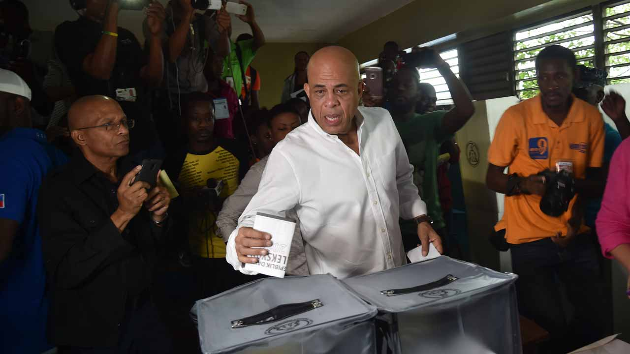 Former Haitian President Michel Martelly casts his ballot at a polling station at the Lycee National in the Petion Ville suburb of Port-au-Prince, Haiti on November 20, 2016 during the presidential and legislative elections. Haitians go to the polls Sunday to elect a president and lawmakers, in hopes of restoring the country to constitutional order after more than a year of political crisis. Nearly 6.2 million voters are eligible to cast their ballots to choose among a vast field of 27 presidential candidates. HECTOR RETAMAL / AFP