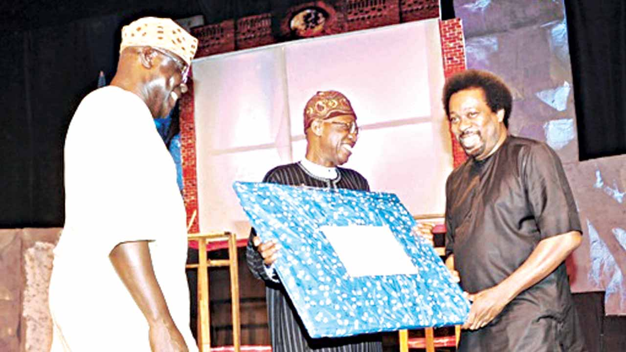 Son of Prof. Wole Soyinka, Mr. Makin Soyinka, receiving National Troupe of Nigeria's (NTN) gift from Minister of Information and Culture, Alhaji Lai Mohammed while NTN's CEO/Artistic Director, Mr. Akin Adejuwon looks on… in Lagos