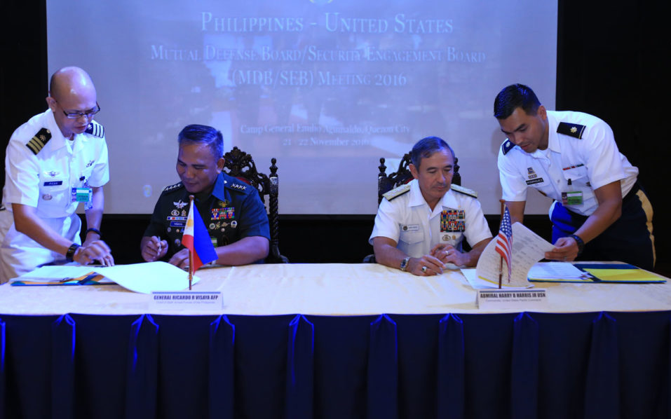 "This handout photo atken on November 22, 2016 and released by Armed Forces of the Philippines-Public Affairs Office (AFP-PAO) shows Philippine military chief General Ricardo Visaya (L) and US Pacific Command chief Admiral Harry Harris signing the activisty list for US and Philippine military, during the Mutual Defence Board (MDB) meeting at the military headquarters in Manila. Philippine-US military ties are still ""robust"" despite threats by President Rodrigo Duterte to sever defence relations between the two allies, Manila's military spokesman said November 22. / AFP PHOTO / AFP-PAO / HO"