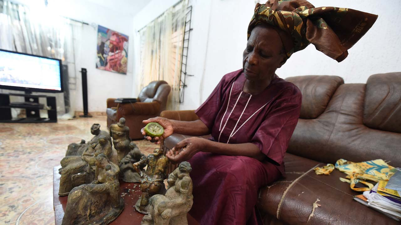 Nigeria's first female bronze caster Princess Elizabeth Olowu, 77, cleans her bronze sculptures with lemon juice in her living room in Benin City, on October 21, 2016. Bronze art made the reputation and the fortune of the ancient royal kingdom of Benin, whose history dates back nearly 1,000 years and whose name was given to Nigeria's smaller, French-speaking neighbour. PIUS UTOMI EKPEI / AFP