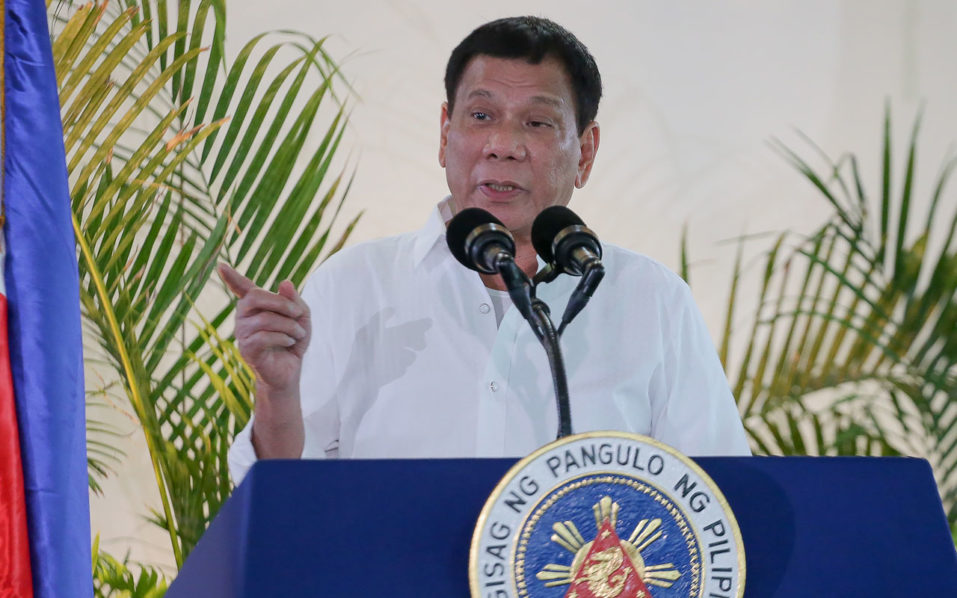"Philippine President Rodrigo Duterte gestures as he delivers a speech, prior to his departure for the APEC summit in Peru, at Davo airport, in southern island of Mindanao on November 17, 2016. Duterte threatened on November 17 to do a Russia and pull his country out of the International Criminal Court, incensed at foreign criticism of alleged extrajudicial killings in his deadly drug war. Russia on November 16 formally withdrew its signature to the ICC's founding Rome Statute, calling the tribunal's work ""one-sided and inefficient"". / AFP PHOTO / MANMAN DEJETO"