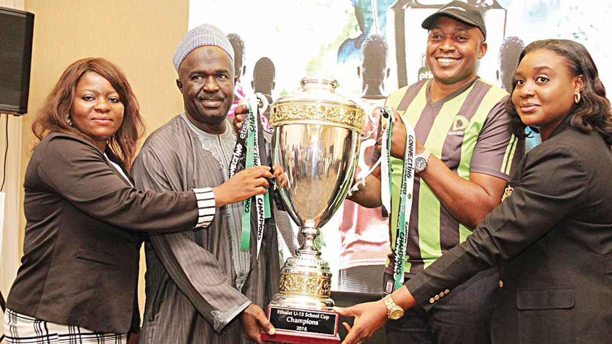 Secretary, Nigerian School Sports Federation (NSSF), Olabisi Joseph (left) and President, Nigerian School Sports Federation (NSSF), Mallam Ibrahim Muhammad, receiving the Champions Trophy from the Etisalat's Director, Brand and Experience, Elvis Ogiemwanye and Head, Events and Sponsorship, Modupe Thani, during the match draws for the Etisalat School U-15 Cup National finals held in Lagos… on Monday.