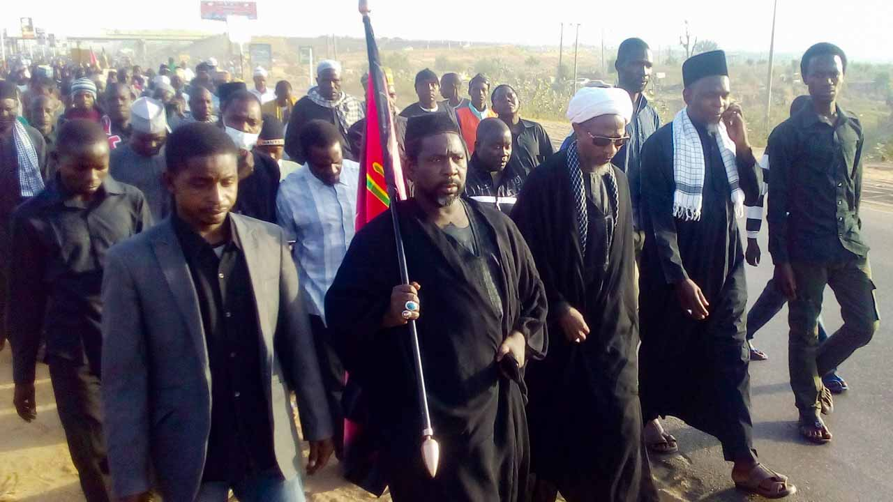 Sanusi Abdulkadir (C), leader of the Kano branch of the pro-Iran Shiite group Islamic Movement of Nigeria (IMN), carries a flag while leading the members of the IMN on the outskirts of the northern Nigerian city of Kano on November 14, 2016, during a 130-kilometers trek to its spiritual headquarters in the city of Zaria for the annual Arbaeen religious festival, which marks the 40th day after Ashura, commemorating the seventh century killing of Prophet Mohammed's grandson, Imam Hussein. At least 10 people were killed and several injured on November 14 when Nigerian police opened fire during clashes with pro-Iranian Shiites outside northern Kano, the latest round of violence involving the group. AMINU ABUBAKAR / AFP