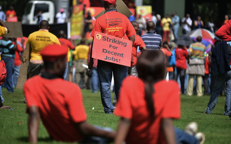 striking members of NUMSA (National Union of Metal Workers of South Africa) demonstrating for better wages in a central district of Johannesburg. South Africa's unemployment rate hit a 13-year high of 27.1 percent in the third quarter, the statistics office said on November 22, 2016, as the country battles economic and political crises. Africa's most advanced economy posted a rise in joblessless of 239,000, bringing the total number of people out of work to 5.9 million, StatsSA said in its quarterly report. / AFP PHOTO / MUJAHID SAFODIEN