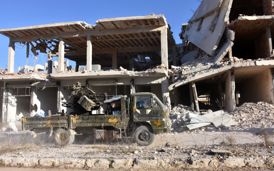 A vehicle of Syrian pro-government forces drives past damaged buildings on November 27, 2016 in the Masaken Hanano district in eastern Aleppo, a day after they resized it from rebel fighters. Syria regime forces seized two new rebel-held districts in Aleppo a day after they retook the largest opposition-controlled neighbourhood in the second city, a monitor said. The capture of Masaken Hanano -- which had been the biggest rebel-held district of Aleppo -- was a major breakthrough in a 13-day regime offensive to retake the entire city. / AFP PHOTO / GEORGE OURFALIAN