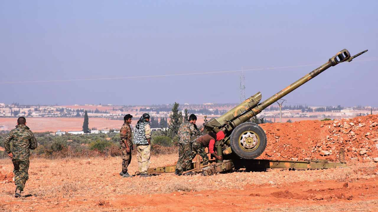 Syrian pro-government fighters fire a Russian 122mm howitzer gun as they advance in the recently recaptured village of Joubah during an offensive towards the area of Al-Bab in Aleppo province, on November 25, 2016. The Syrian army advanced in Aleppo, pounding the rebel-held east with strikes that killed dozens and added to the despair for more than 250,000 civilians under siege. GEORGE OURFALIAN / AFP