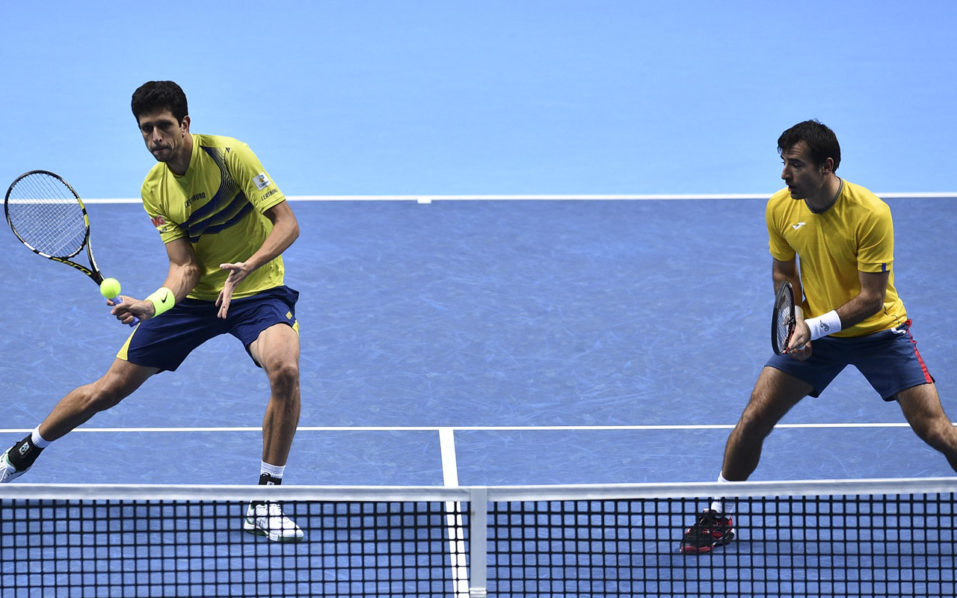 Brazil's Marcelo Melo (L) returns as his partner Croatia's Ivan Dodig (R) looks on against Britain's Jamie Murray and Brazil's Bruno Soares during their round robin stage men's doubles match on day five of the ATP World Tour Finals tennis tournament in London on November 17, 2016. / AFP PHOTO / Glyn KIRK