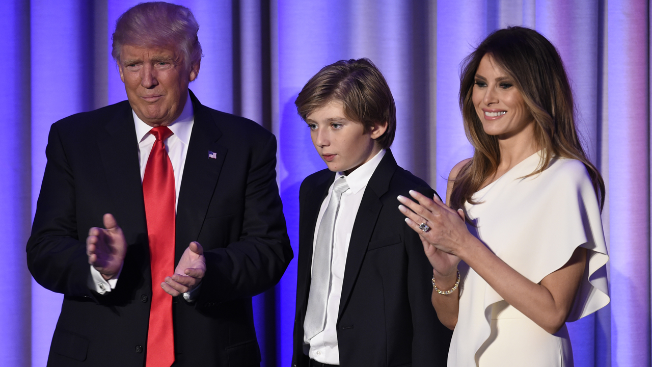 US President-elect Donald Trump arrives with his son Baron and wife Melania at the New York Hilton Midtown in New York on November 8, 2016. Trump stunned America and the world Wednesday, riding a wave of populist resentment to defeat Hillary Clinton in the race to become the 45th president of the United States. / AFP PHOTO / SAUL LOEB