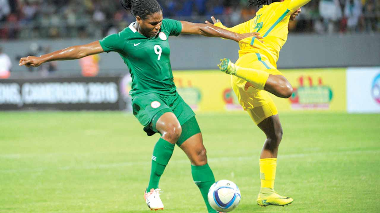 Super Falcons' goal scorer, Desire Oparanozie (left) takes on a Banyana Banyana' defender during Nigeria's semifinal game against South Africa at the on-going African Women Nations Cup in Limbe, Cameroun…yesterday. 				         PHOTO: CAF.