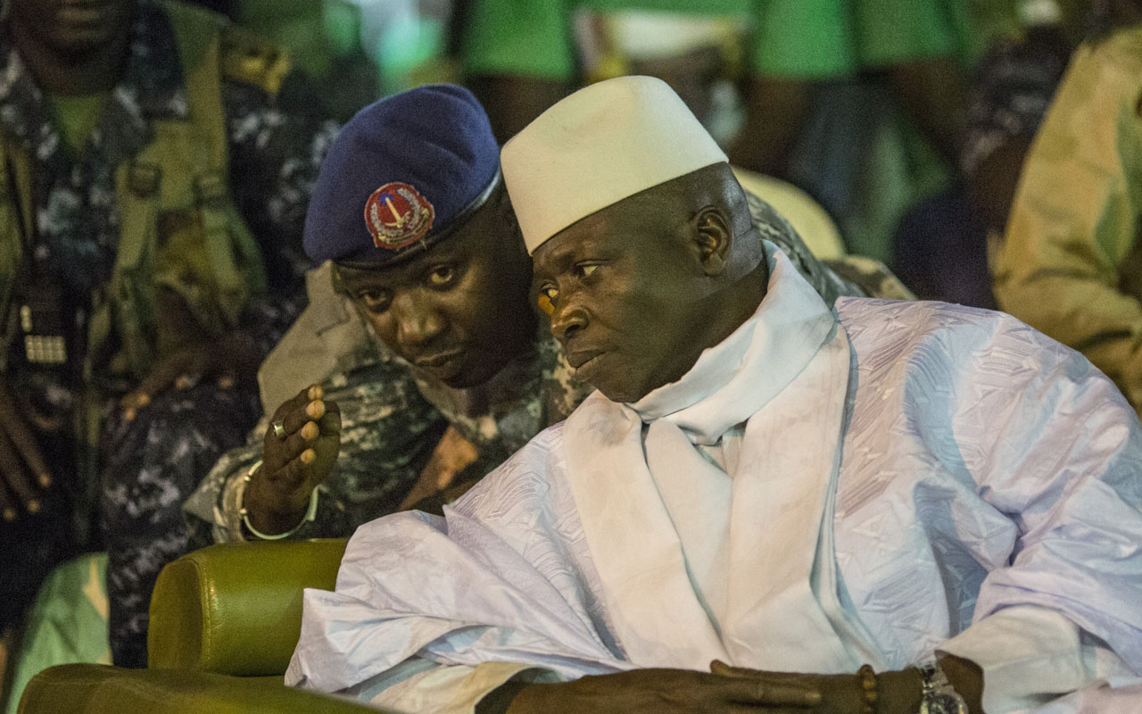 "Incumbent Gambian President Yahya Jammeh listens to one of his aides in Banjul on November 29, 2016, during the closing rally of the electoral campaign of the Alliance for Patriotic Reorientation and Construction (APRC). More than 880,000 voters are expected to cast their ballots when the west African country goes to the polls on December 1, 2016. Jammeh has won four elections with his ruling Alliance for Patriotic Reorientation and Construction, following a 2002 constitutional amendment lifting term limits. Rights bodies and media watchdogs including Reporters Without Borders (RSF) accuse Jammeh of cultivating a ""pervasive climate of fear"" and of crushing dissent against his regime, one cause of the mass exodus of Gambian youths to Europe. / AFP PHOTO / MARCO LONGARI"