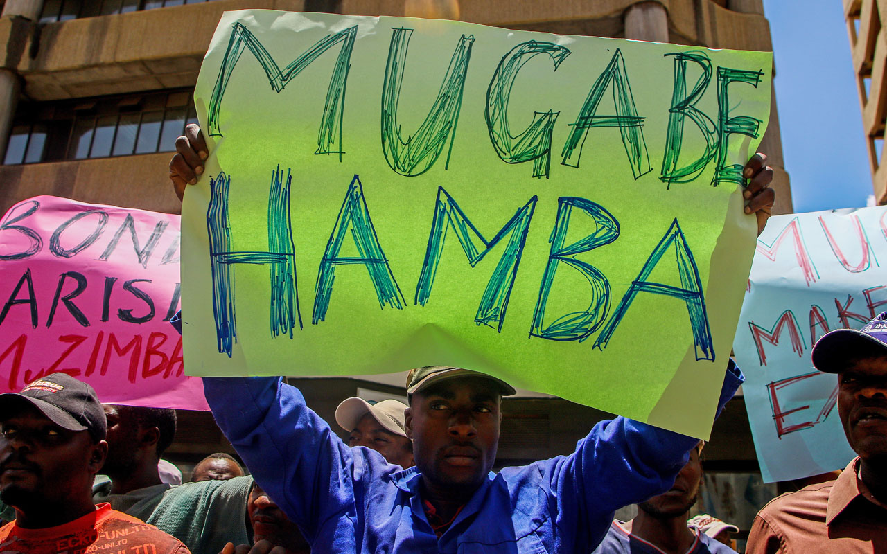 "Protesters hold signs during a demonstration by opposition parties against the introduction of bond notes as a currency in Harare, on November 30, 2016. A token currency issued in Zimbabwe this week to ease critical cash shortages has brought little relief as desperate customers queue for hours to withdraw money while some traders reject the new notes. The central bank on November 28, 2016 issued $10 million in US dollar-equivalent ""bond notes"", ignoring resistance from citizens and companies who feared a return to the days of hyperinflation. / AFP PHOTO / Jekesai Njikizana"