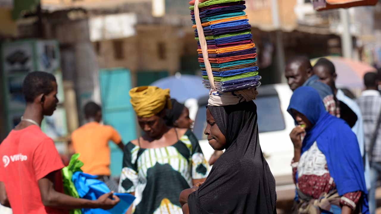 A seller carries folded fabric on her head through the Serrekunda marketplace in Banjul on December 4, 2016. President Yahya Jammeh scored only half his previous box office tally in last week's election, handing victory to opposition coalition leader Adama Barrow. PHOTO: SEYLLOU / AFP