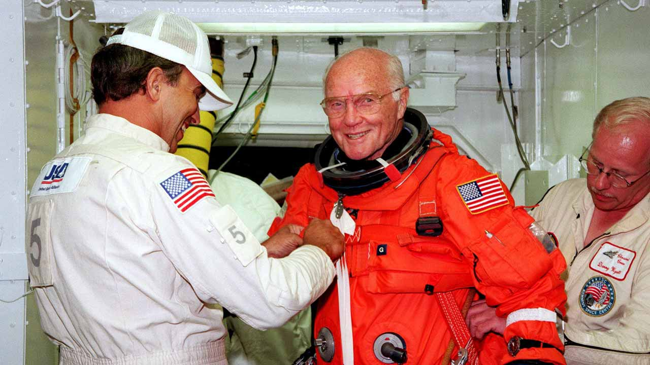 (FILES) This file photo taken on October 9, 1998 shows US astronaut and Senator John Glenn getting a hand from white room technicians moments before boarding the US space shuttle Discovery. Glenn, who made history twice as the first American to orbit the Earth and the first senior citizen to venture into space, has died at the age of 95, the Ohio State University's John Glenn College of Public Affairs said on December 8, 2016. PHOTO: HO / NASA / AFP