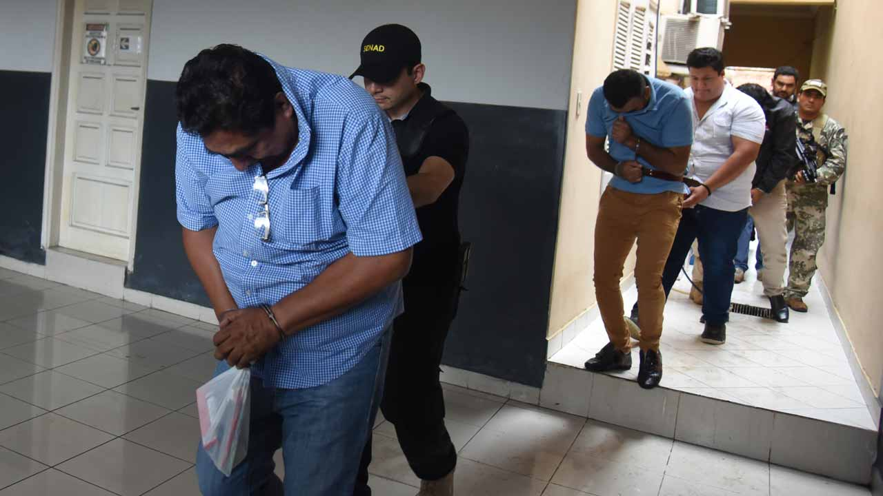 Mexican Martin Huerta (L) is taken into custody by police after declaring in Asuncion on December 9, 2016. Four Mexicans presumably linked to the Sinaloa cartel were arrested Thursday, among them Waine Gallien, pointed as a cartel leader and 308kg of cocaine were seized. PHOTO: NORBERTO DUARTE / AFP