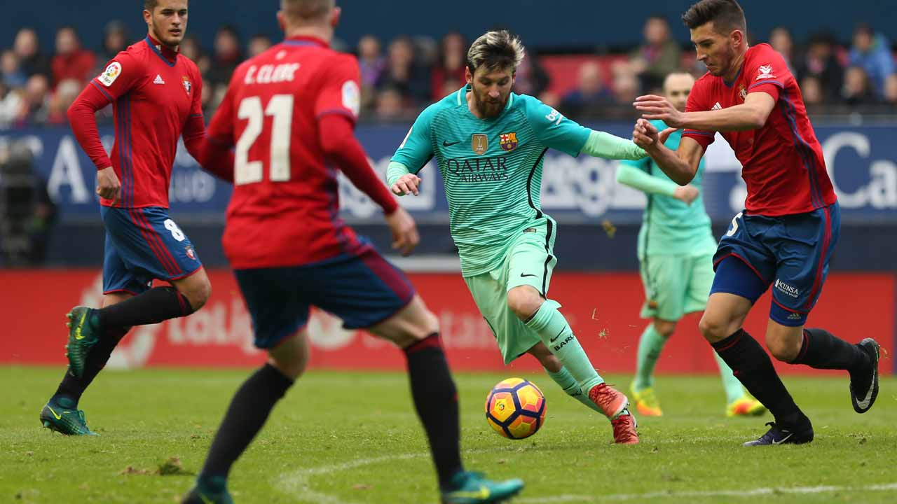 Barcelona's Argentinian forward Lionel Messi (C) vies with Osasuna's defender David Garcia during the Spanish league football match CA Osasuna vs FC Barcelona at the Reyno de Navarra (El Sadar) stadium in Pamplona on December 10, 2016. PHOTO: CESAR MANSO / AFP
